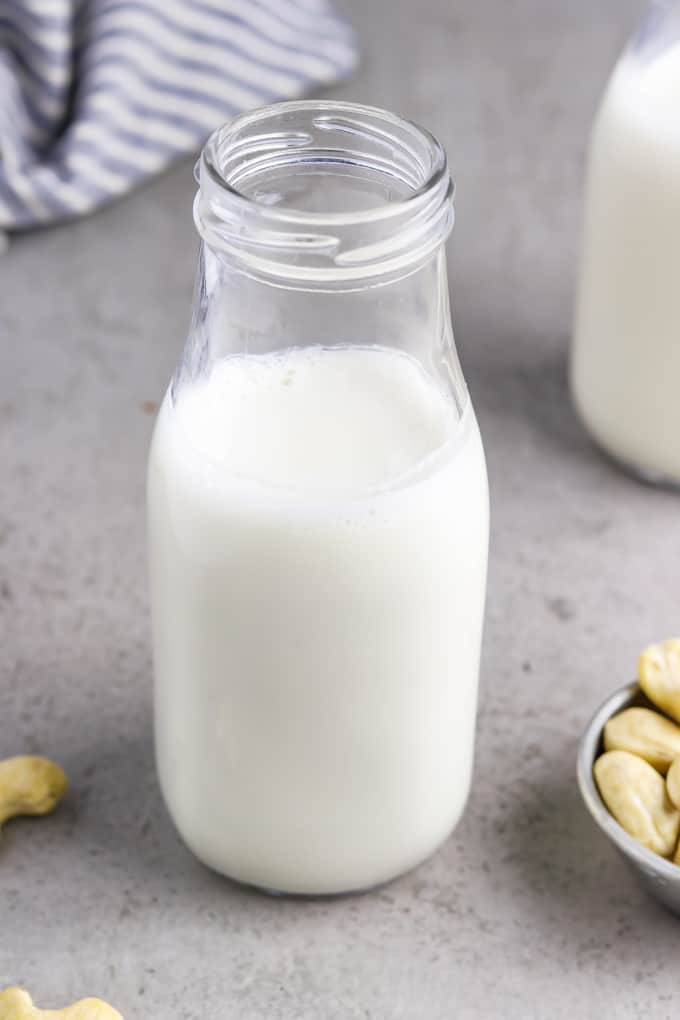 cashew milk in a glass bottle with whole cashews on the side.