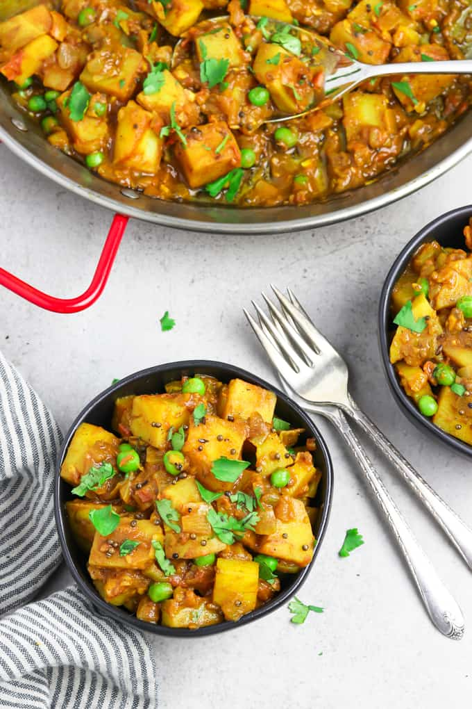 Overhead view of two bowls of bombay potatoes with forks in the middle. Pan of potatoes in the background.