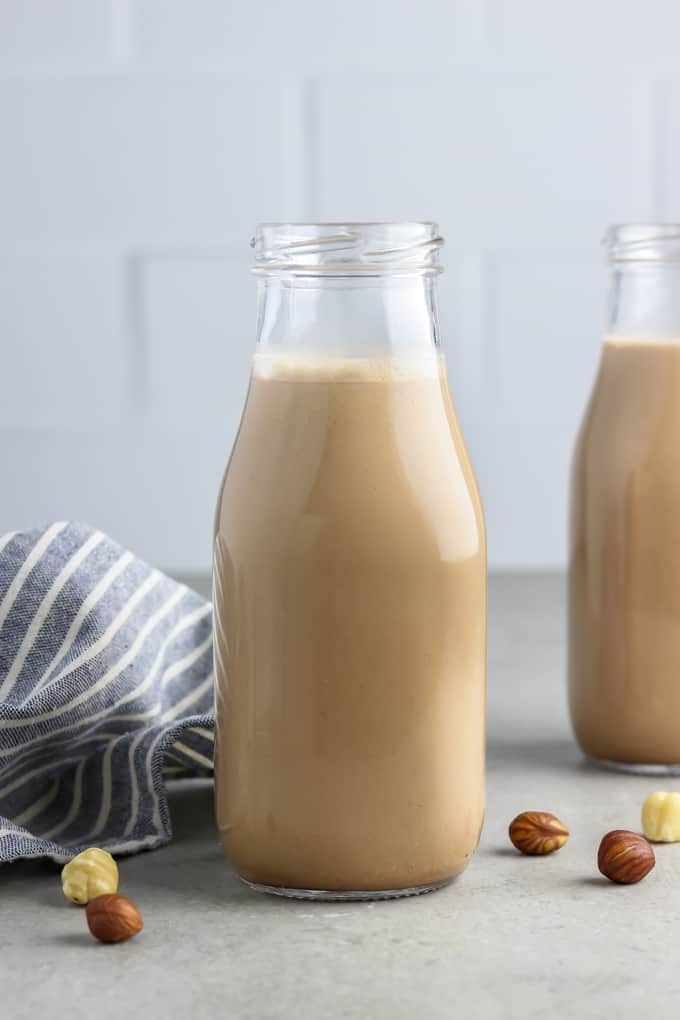 Two bottles filled with chocolate hazelnut milk. Striped napkin on the side.