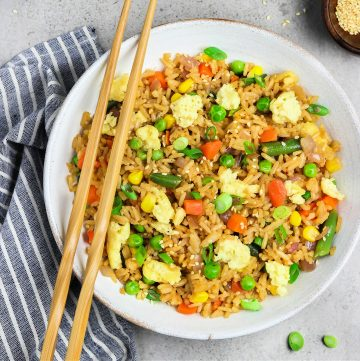 vegan fried rice in a white bowl with chopsticks on the side.