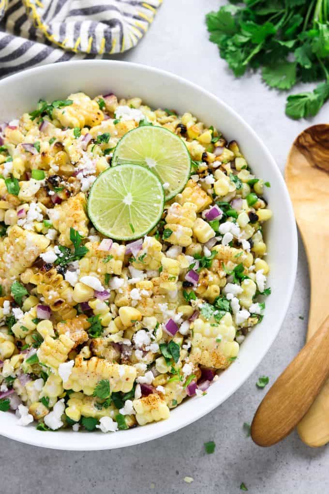 Overhead view of corn salad in a white serving bowl topped with fresh lime. Wooden spoon and napkin on the side.