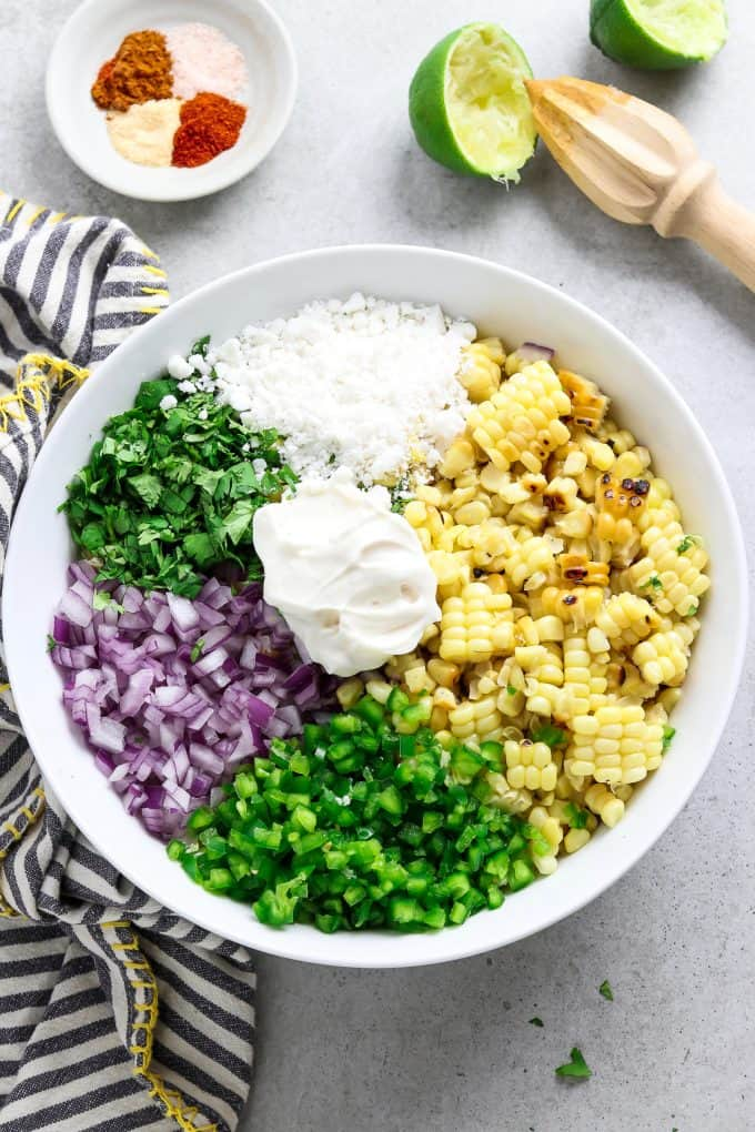 Overhead view of corn salad that hasn't been combined yet. Ingredients are all separate.