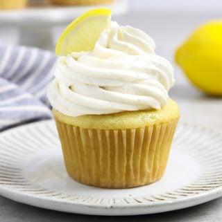 vegan lemon cupcake on a white plate. Fresh lemon in the background.