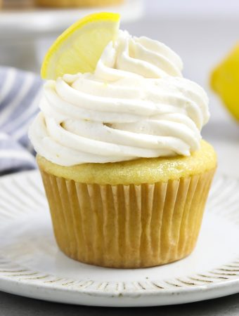 vegan lemon cupcake on a white plate. Fresh lemon in the background.