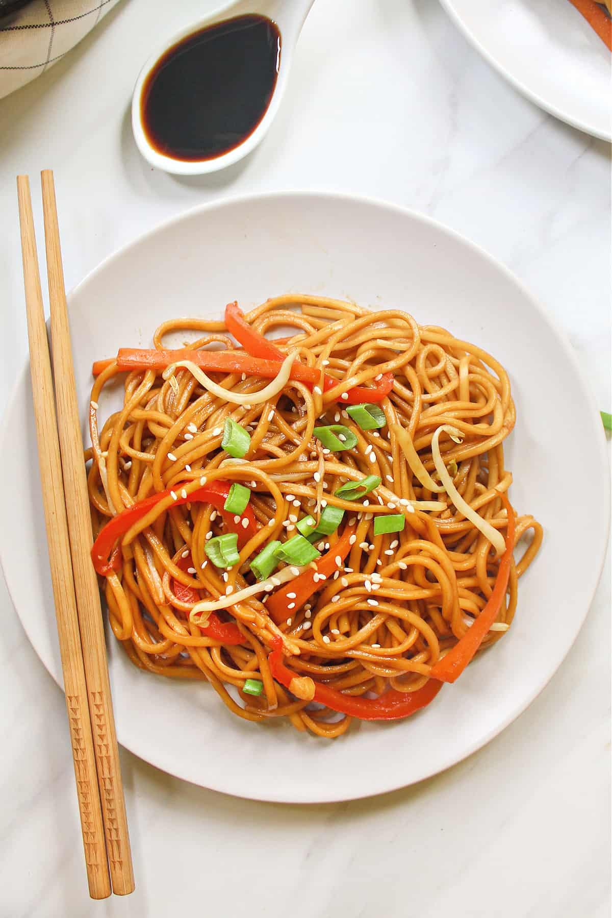 Overhead view of fully cooked vegetable lo mein on a white plate with chopsticks on the side.
