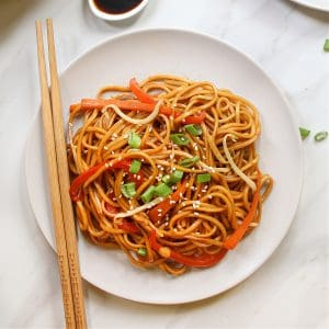 overhead view of vegan lo mein on a white plate with chopsticks on the side.