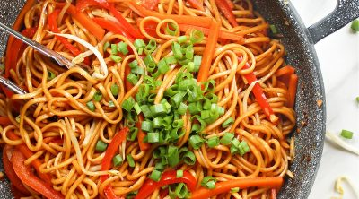 overhead view of lo mein in a wok, topped with green onions.