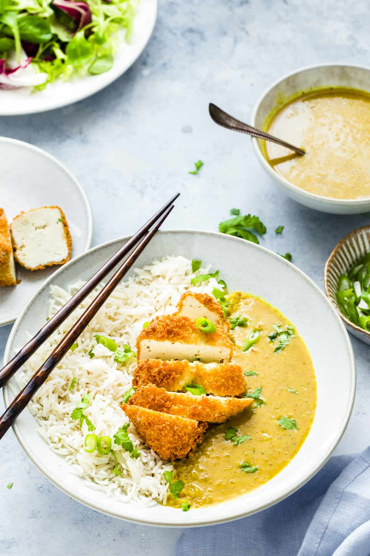 tofu katsu curry in a white bowl with rice on the side. Chop sticks on top of the bowl.