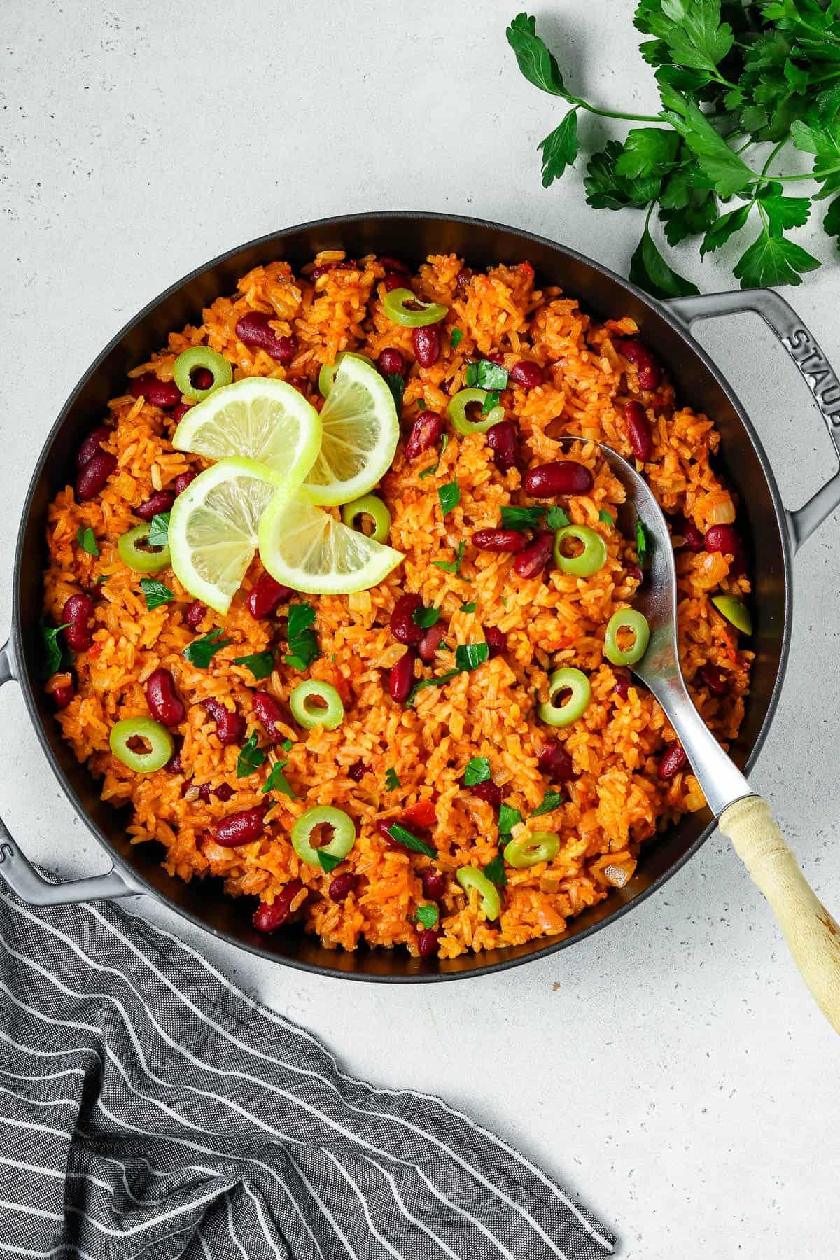 Overhead view of fully cooked rice and beans in a gray pan. Lemon wedges on top.