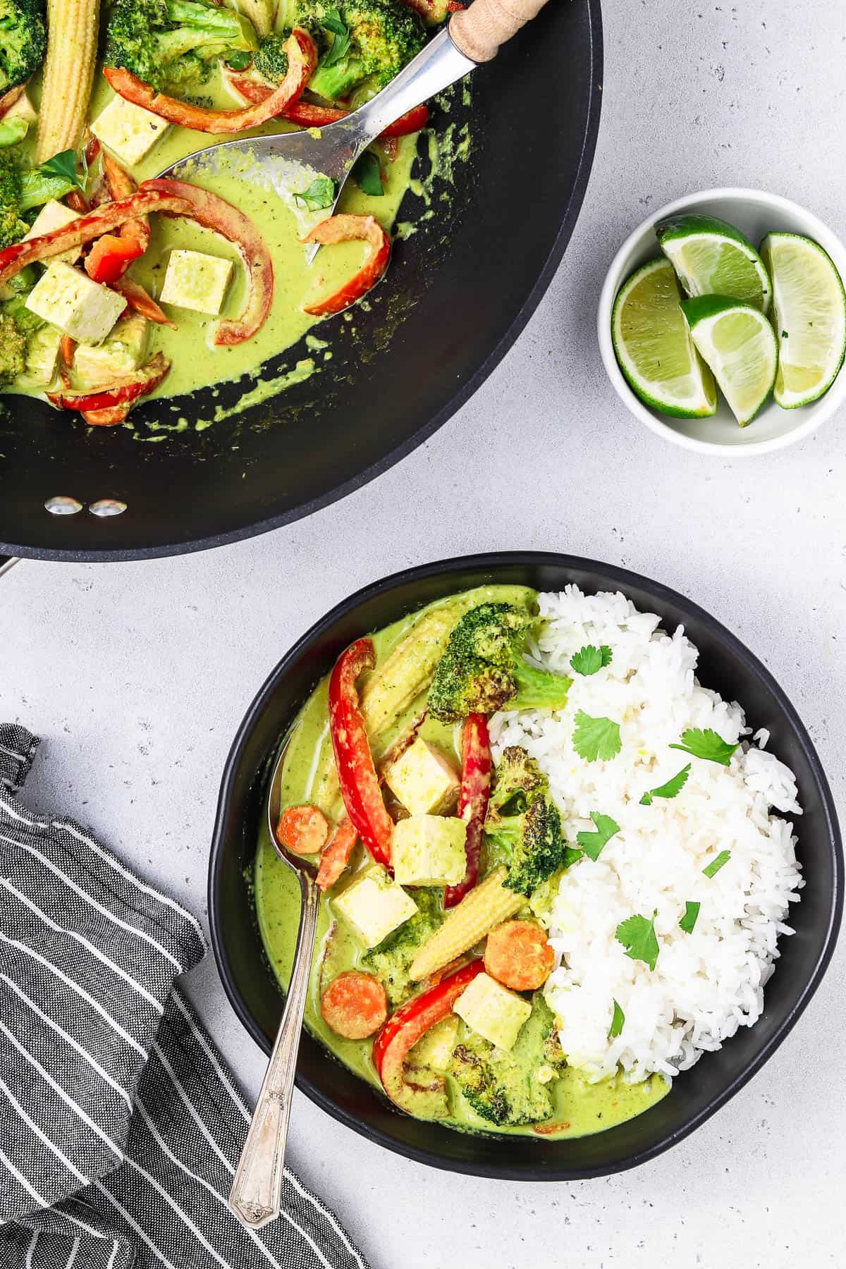 A bowl and wok filled with vegan Thai green curry. Striped napkin and lime on the side.
