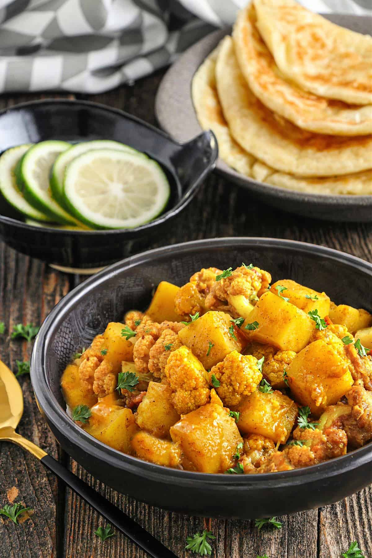 Side view of Aloo Gobi in a bowl. Naan and limes in the background.
