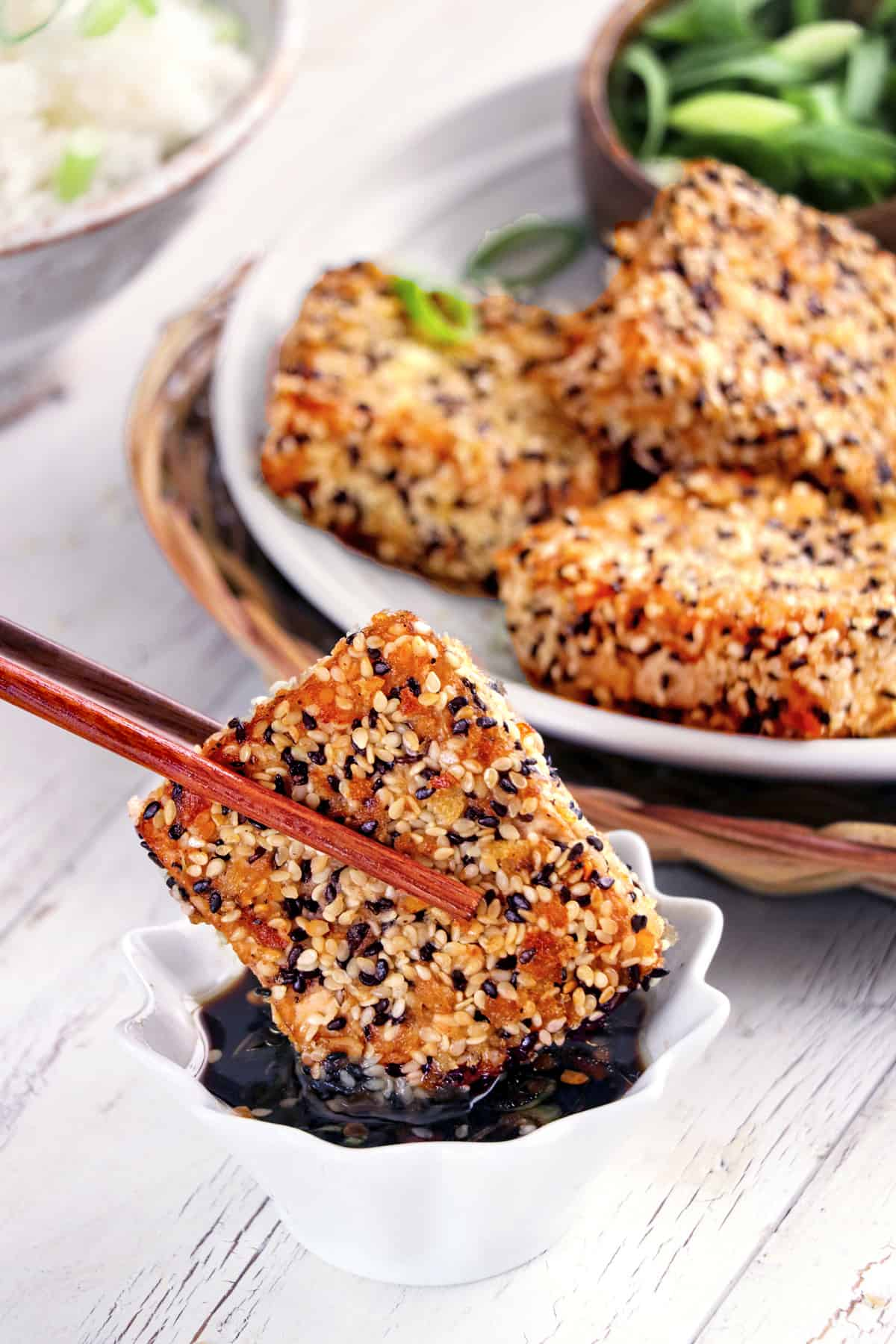 A piece of sesame crusted tofu being dipped into sauce with chopsticks.