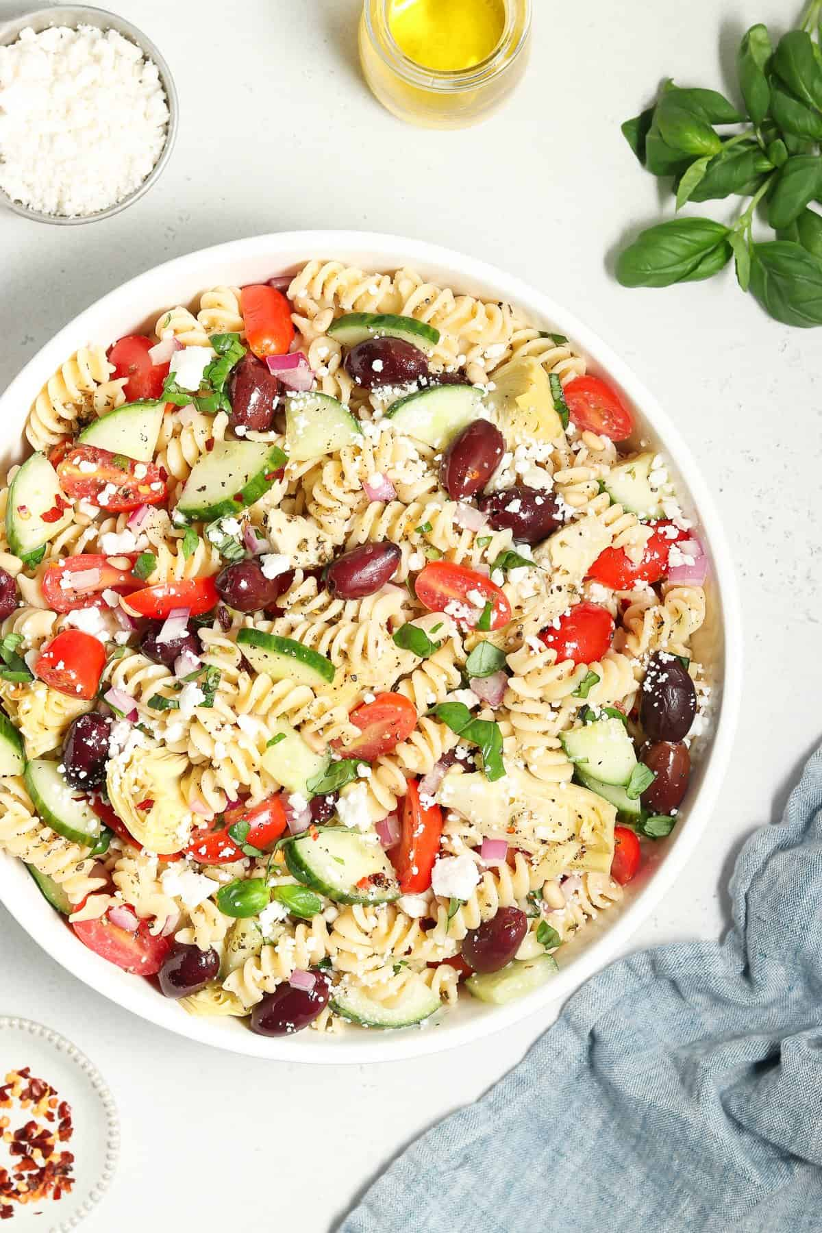 Close up and overhead view of pasta salad in a white bowl. Basil and napkin on the side.