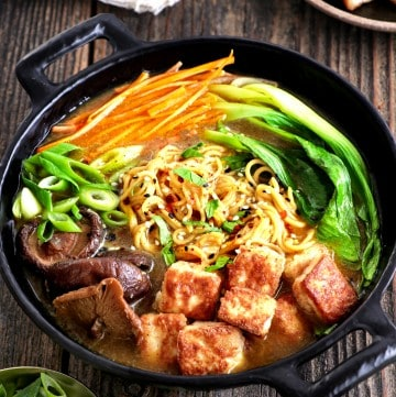 Side view of fully assembled vegan ramen in a black bowl.