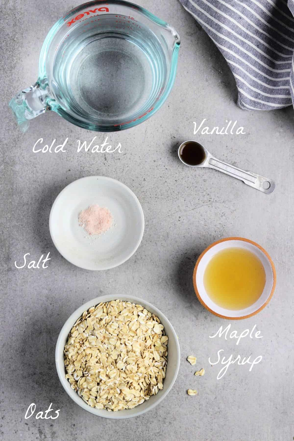 All ingredients to make oat milk on a stone table top.