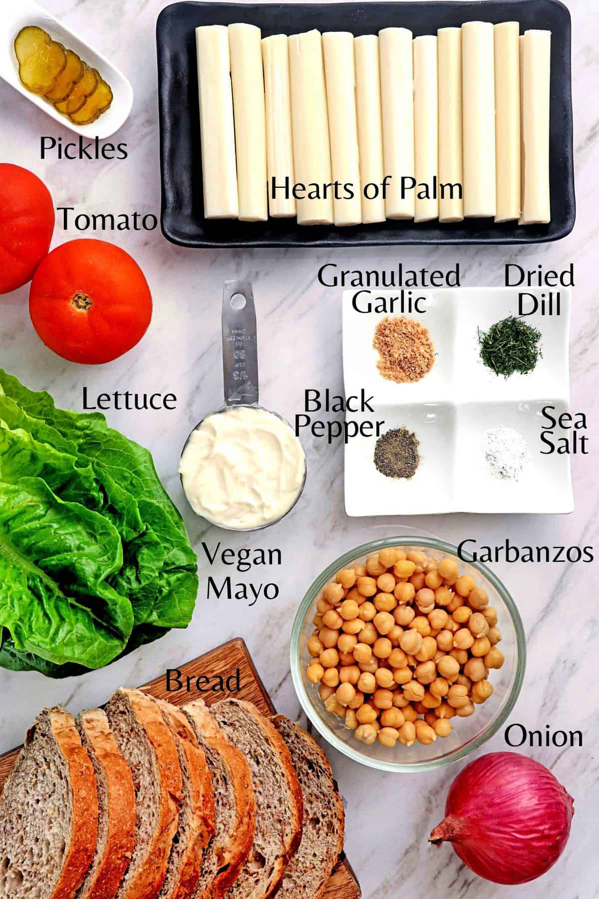 All ingredients to make a vegan tuna sandwich on a marble table top.