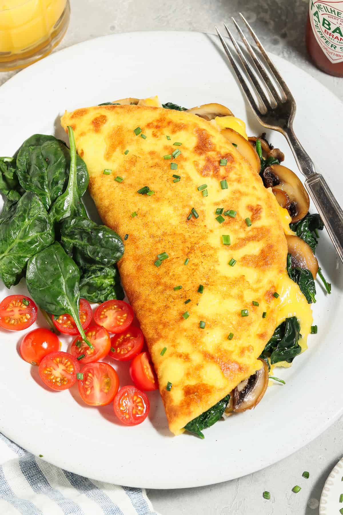 Close up view of fully cooked JUST Egg omelette on a white plate with spinach and tomatoes on the side.