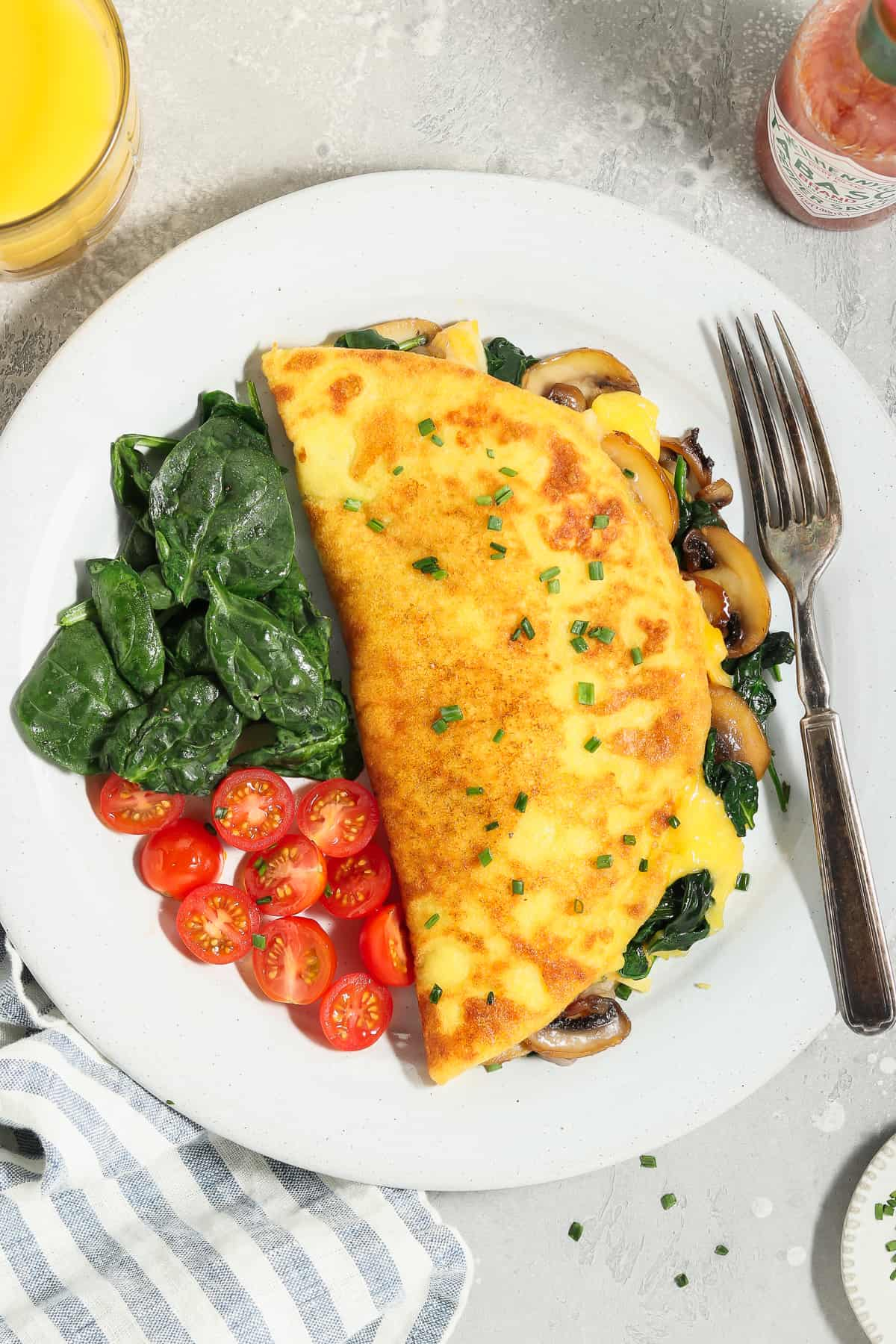 Overhead view of a JUST Egg omelette on a white plate with spinach and tomatoes on the side.