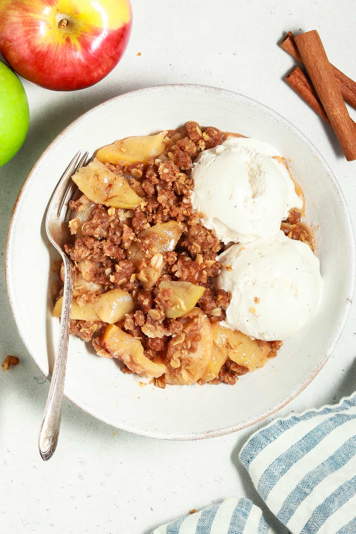 Overhead view of vegan apple crisp in a white bowl with vanilla ice cream on the side.