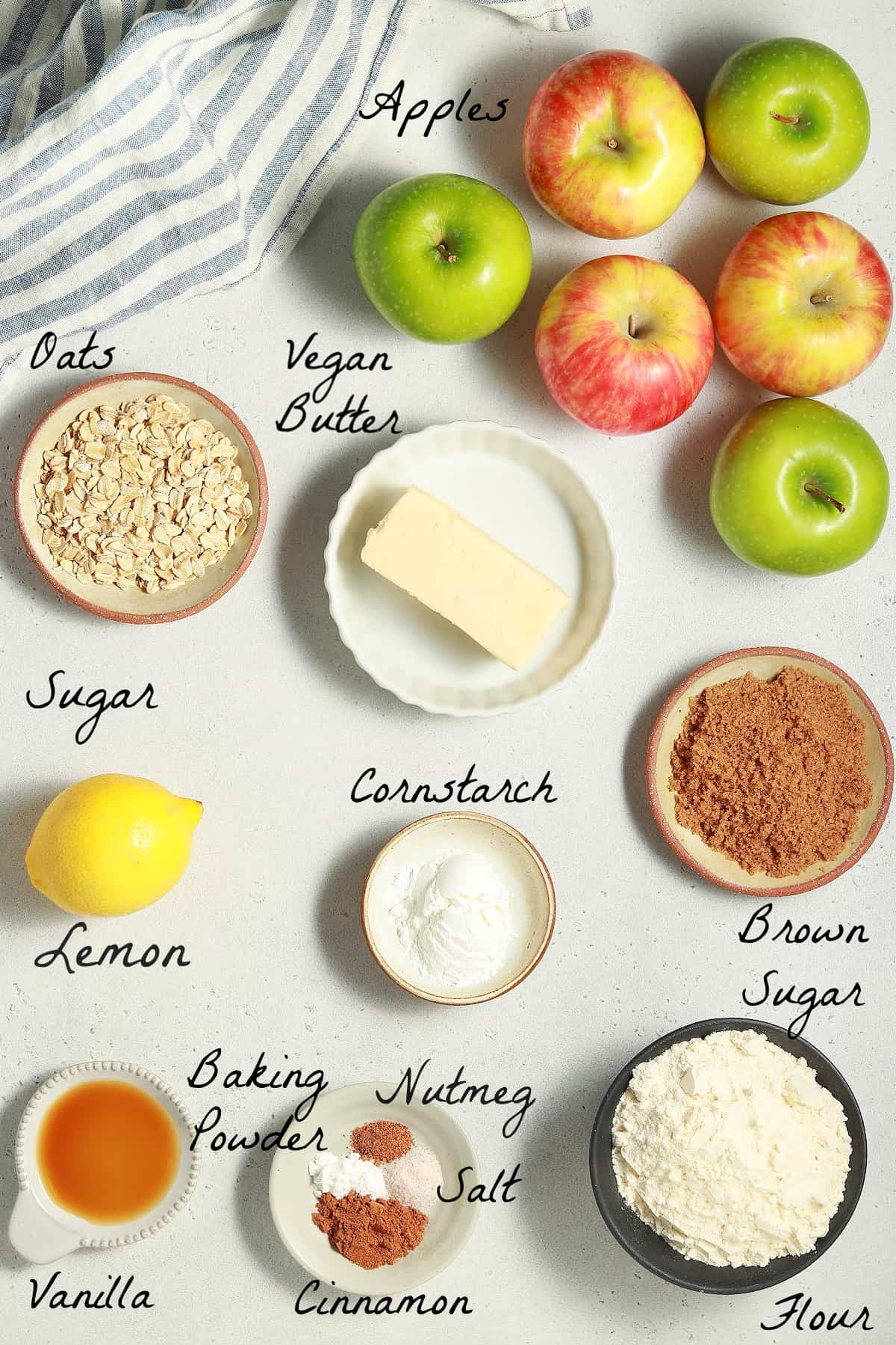 All ingredients to make the apple crisp on a stone table top.