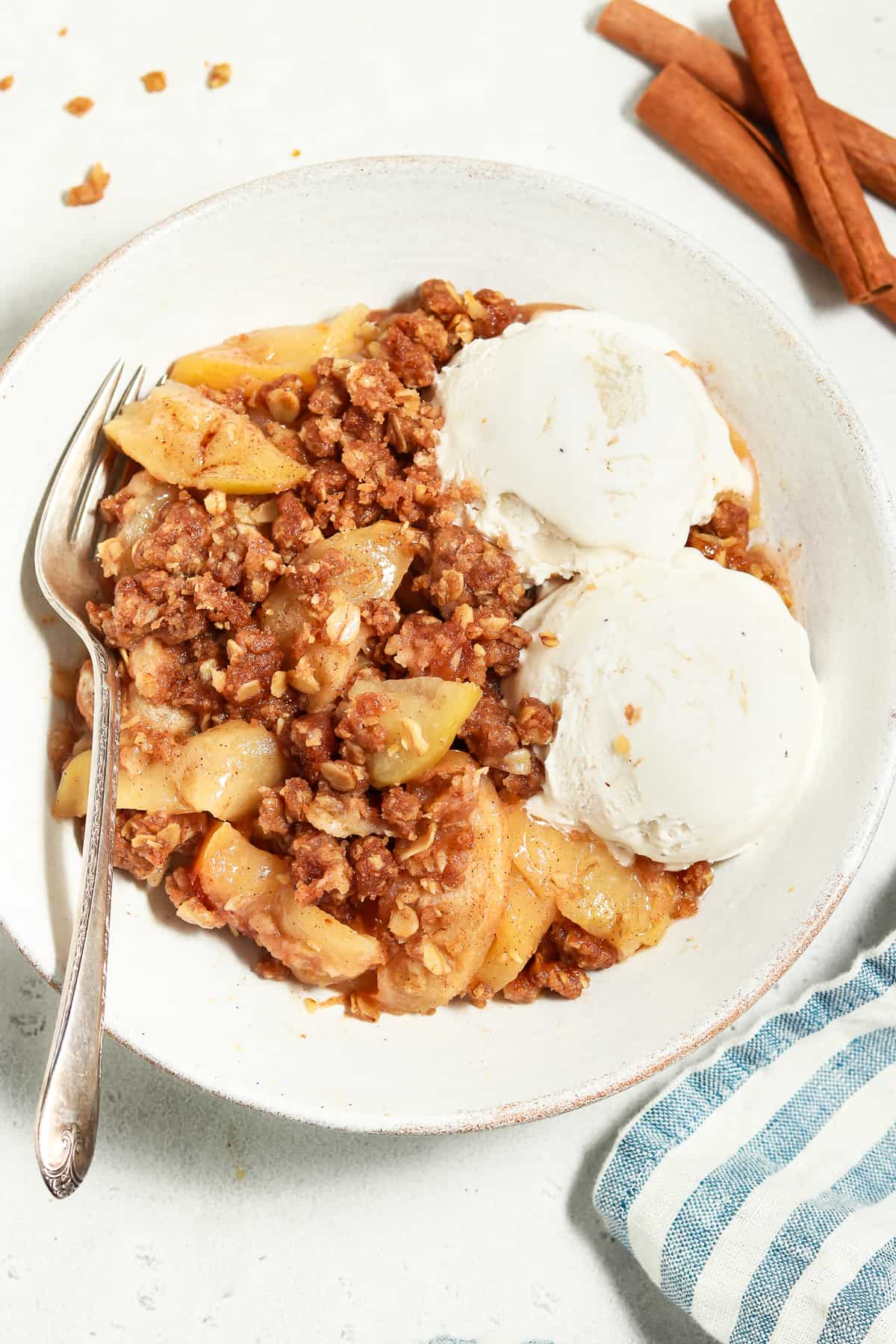Close up view of apple crisp in a white bowl with ice cream on the side.