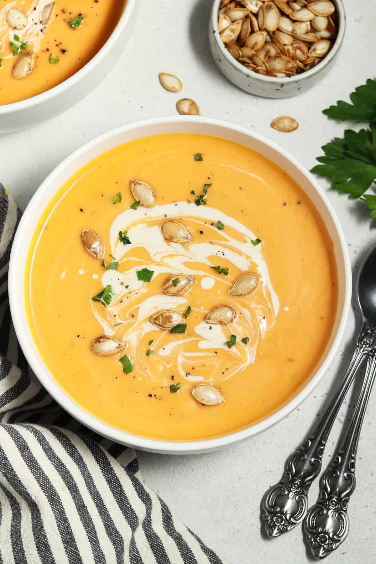 Overhead view of fully cooked butternut squash soup in a white bowl. Seeds and parsley on top.